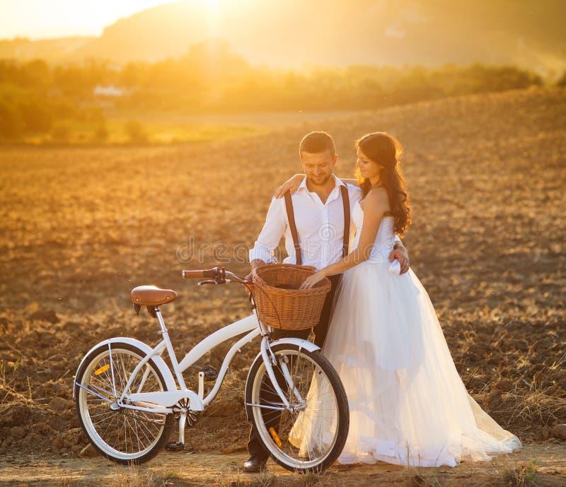 Braut und Bräutigam mit einer weißen Hochzeit fahren rad lizenzfreies stockfoto