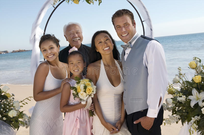 Braut und Bräutigam mit Familie auf Strand (Porträt) stockfotografie