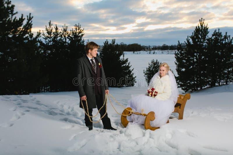 Braut und Bräutigam mit großem hölzernem Schlitten stockfotografie