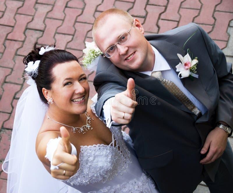 Braut und Bräutigam mit ihren Daumen oben lizenzfreie stockfotos