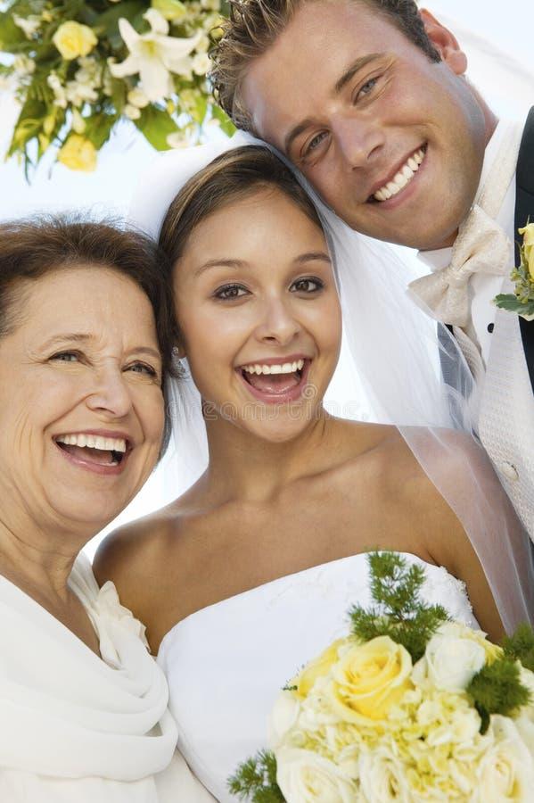 Braut und Bräutigam mit Mutter draußen (Nahaufnahme) (Porträt) stockfotografie