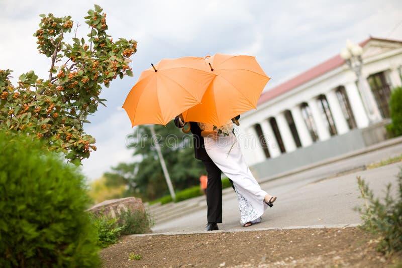 Braut und Bräutigam mit orange Regenschirmen stockfotografie