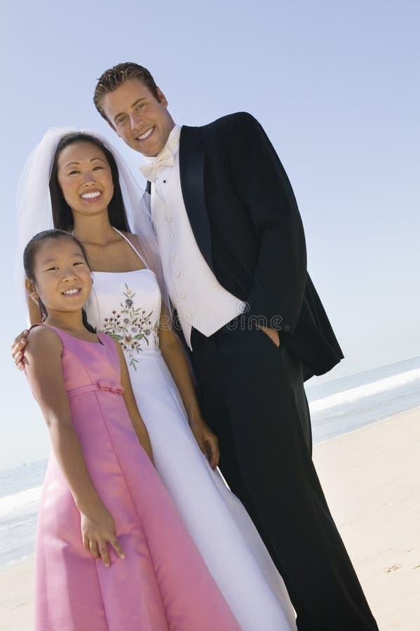 Braut und Bräutigam mit Schwester auf Strand stockfotos