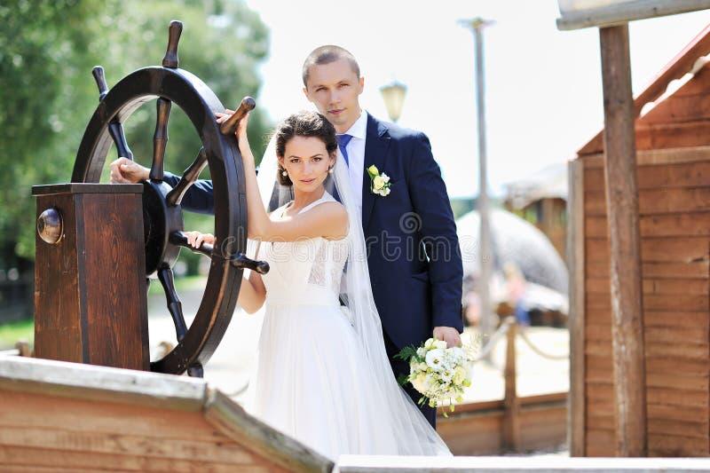 Braut und Bräutigam nahe versenden Lenkrad lizenzfreie stockfotos