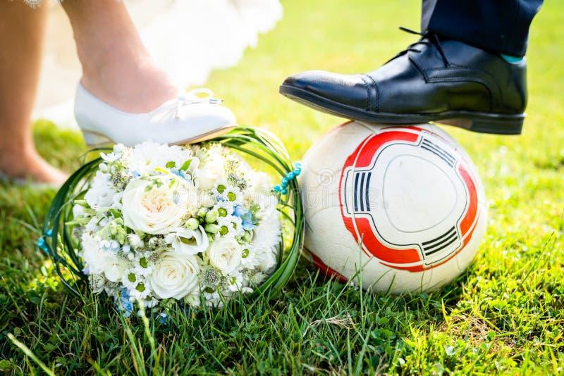 Braut und Bräutigam setzten ihre Füße auf den Fußball lizenzfreies stockfoto