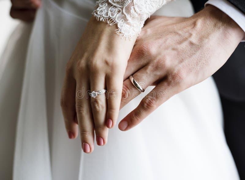 Braut-und Bräutigam-Showing Their Engagement-Eheringe auf Händen lizenzfreies stockfoto