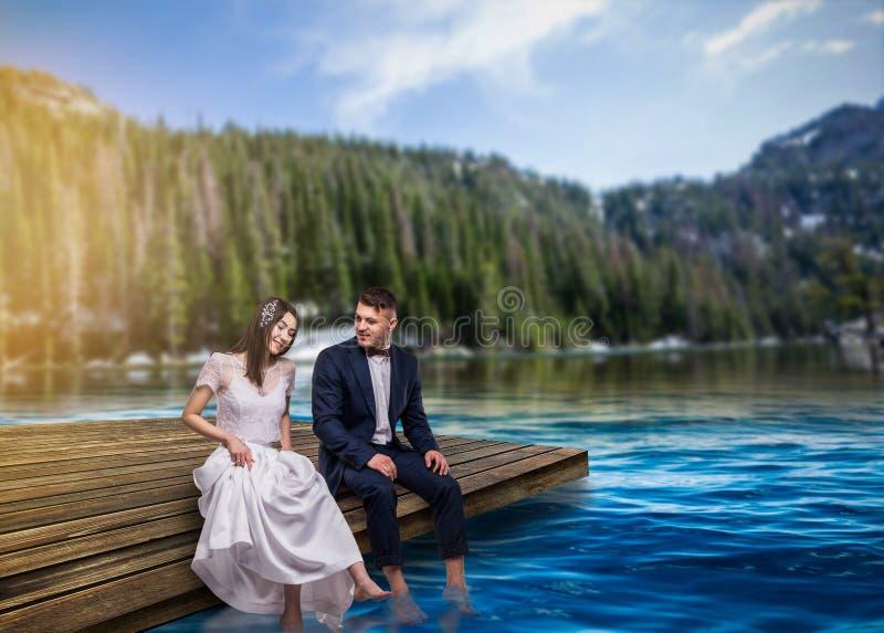 Braut und Bräutigam sitzen auf dem Pier, romantische Szene stockfoto