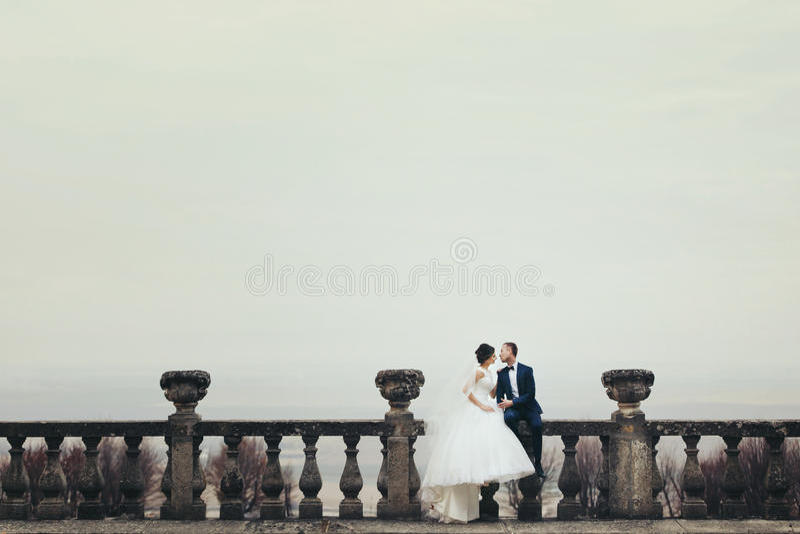 Braut und Bräutigam sitzen auf dem Steinbalkon mit einem tiefen farbigen Himmel stockbilder