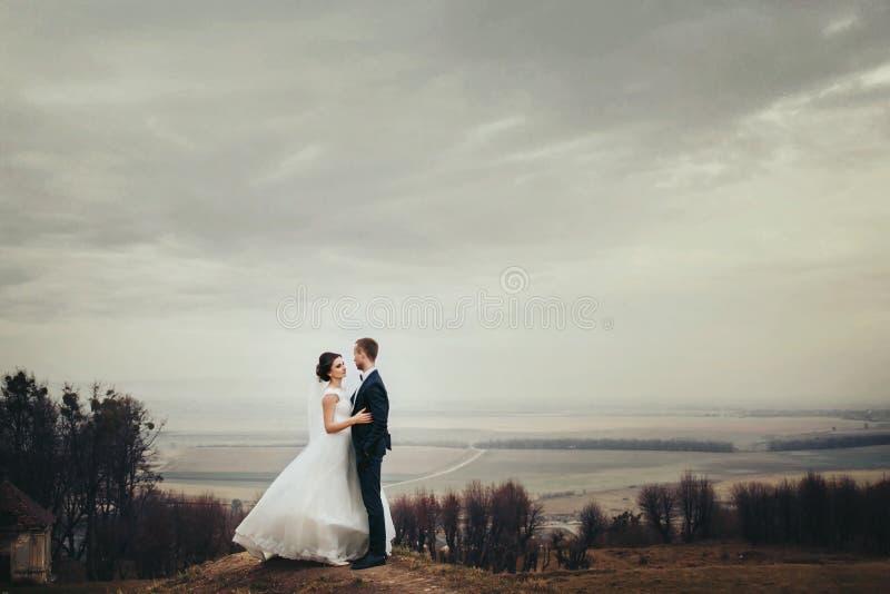 Braut und Bräutigam stehen auf dem Hügel mit großer Herbstlandschaft sind stockbilder