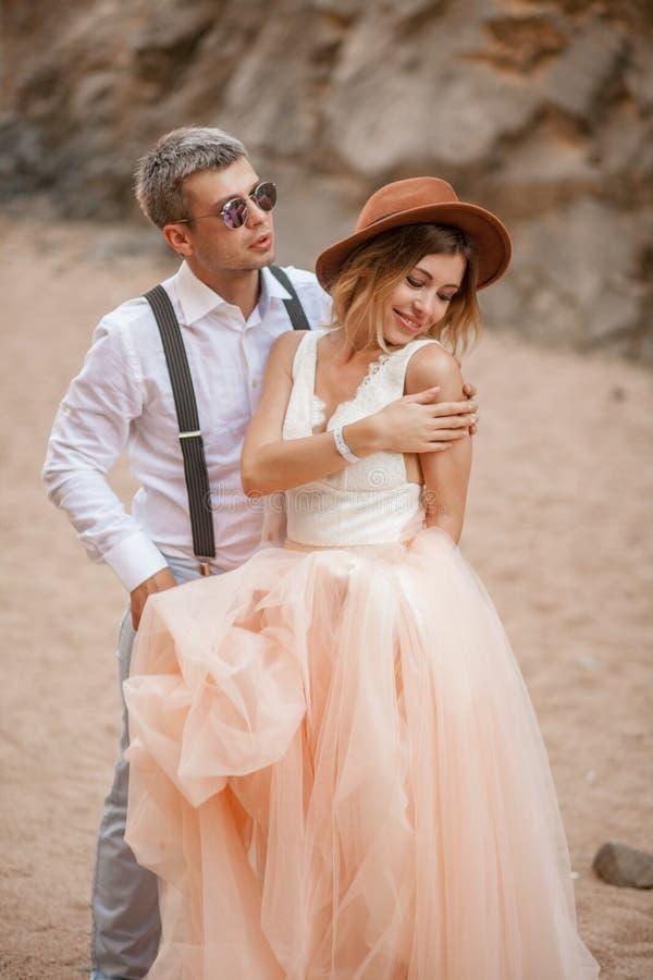 Braut und Bräutigam stehen und lächeln in der Schlucht gegen Hintergrund von Felsen nahaufnahme stockfotos
