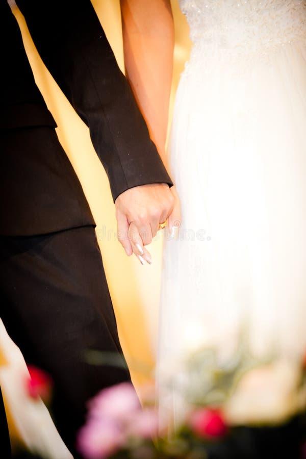 Braut und Bräutigam tragen weißes Kleider- und Weißanzugshändchenhalten auf Hochzeitstagzeremonie lizenzfreie stockfotos
