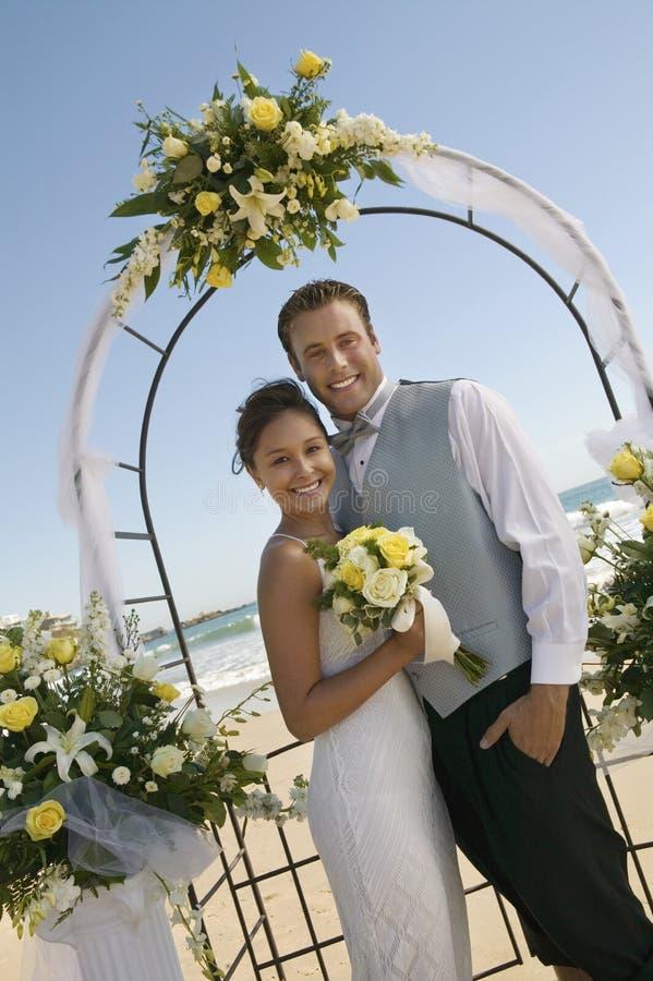Braut und Bräutigam unter Torbogen auf Strand (Porträt) stockbild