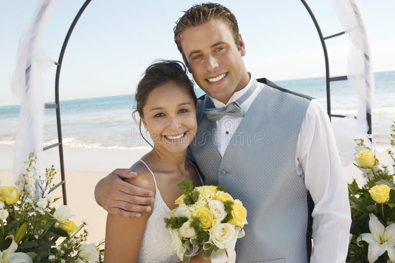 Braut und Bräutigam unter Torbogen auf Strand (Porträt) stockfoto