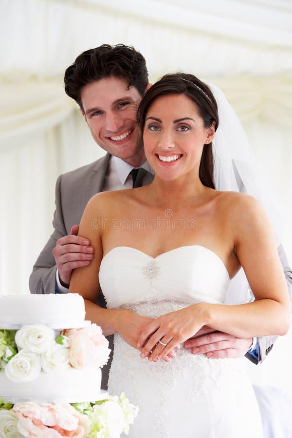 Braut und Bräutigam With Wedding Cake an der Aufnahme lizenzfreie stockfotografie