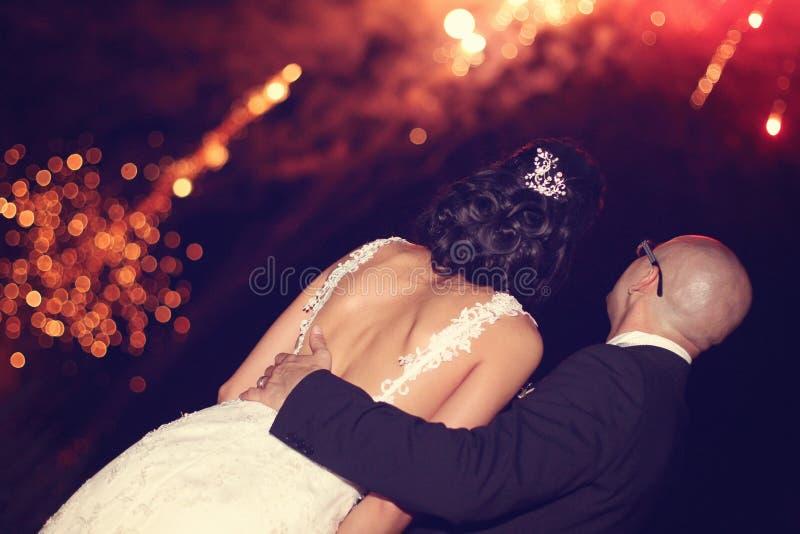 Braut und Bräutigam, welche die Feuerwerke aufpassen stockbilder