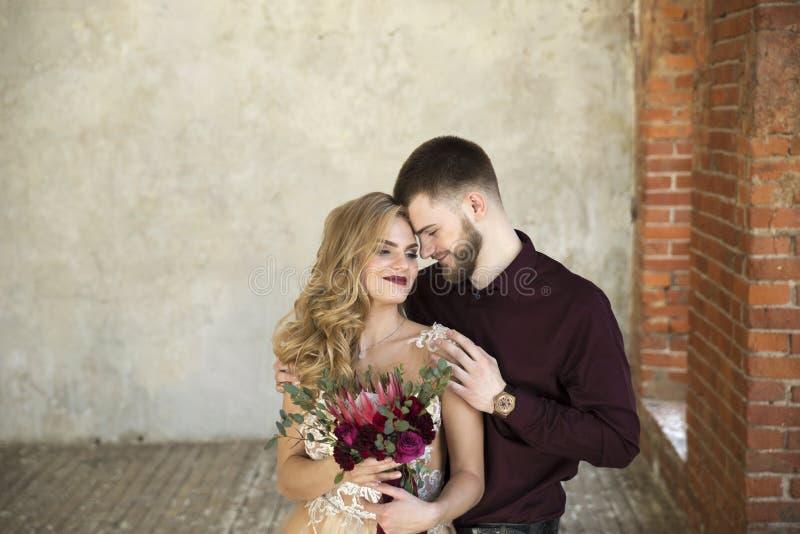Braut und Bräutigam werfen nahe Fenster und Weinlesebacksteinmauer auf stockbild