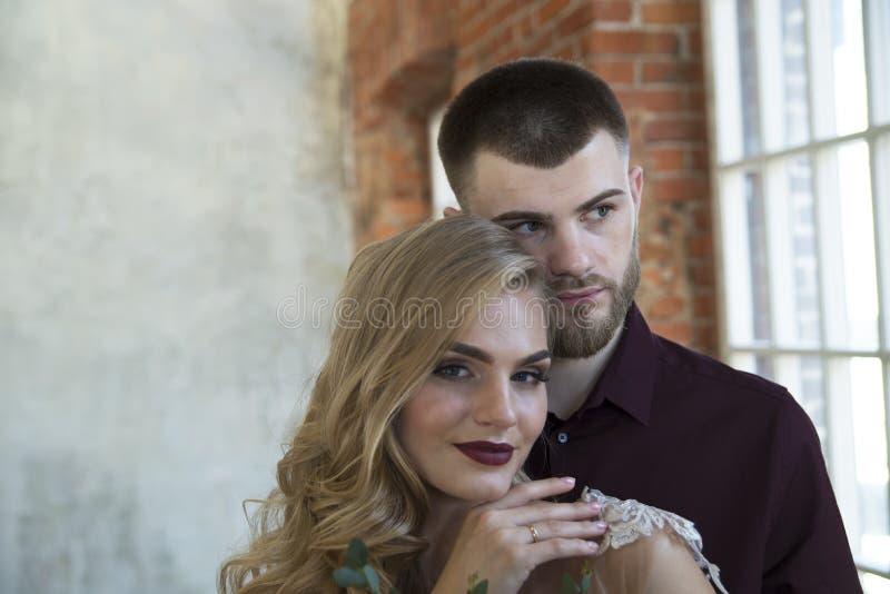 Braut und Bräutigam werfen nahe Fenster und Weinlesebacksteinmauer auf stockfotografie
