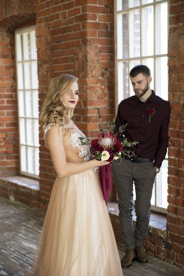 Braut und Bräutigam werfen nahe Fenster und Weinlesebacksteinmauer auf stockfotos