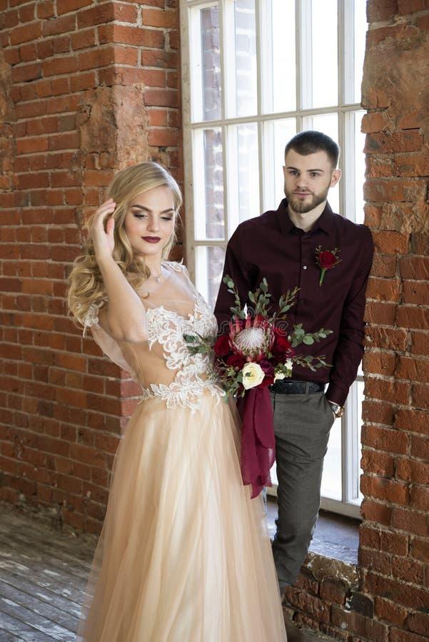 Braut und Bräutigam werfen nahe Fenster und Weinlesebacksteinmauer auf lizenzfreies stockfoto