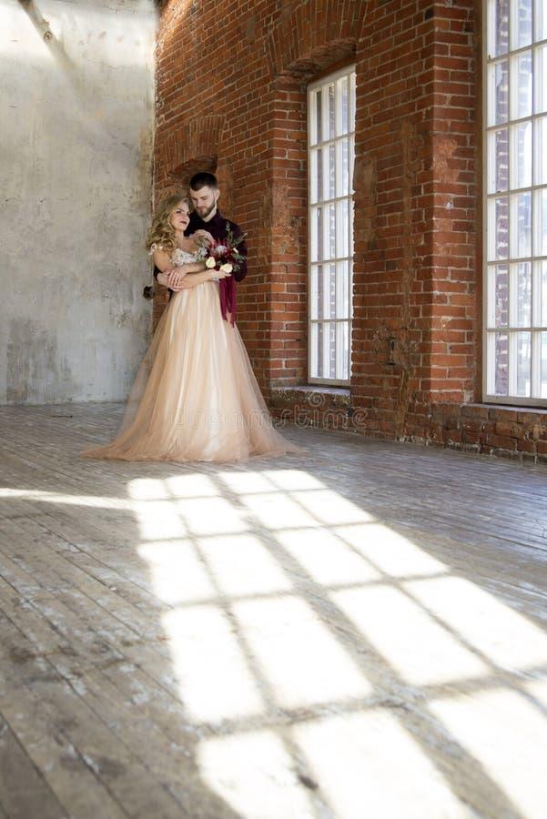 Braut und Bräutigam werfen nahe Fenster und Weinlesebacksteinmauer mit sha auf lizenzfreie stockbilder