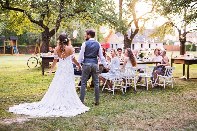 Braut- und Bräutigamhändchenhalten am Hochzeitsempfang draußen im Hinterhof stockbilder