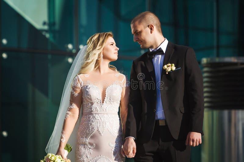 Braut- und Bräutigamhändchenhalten nahe dem modernen Gebäude stockfoto