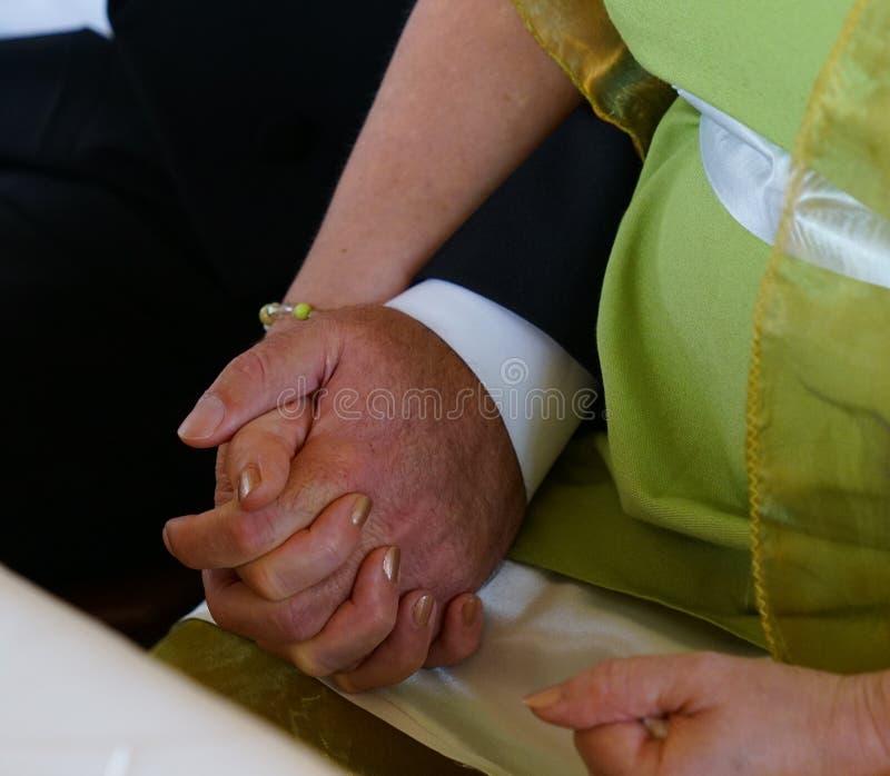 Braut- und Bräutigamhändchenhalten während der Trauung im Zivilregisteramt stockbilder