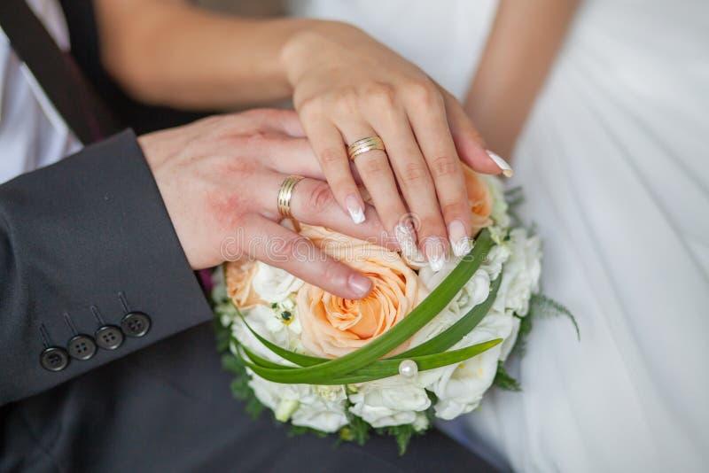 Braut- und Bräutigamhände mit Eheringen und Blumenstrauß von Blumen lizenzfreie stockfotografie