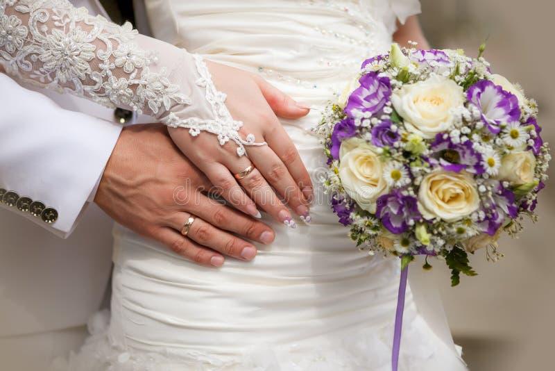 Braut- und Bräutigamhände mit Hochzeitsblumenstrauß und -ringen stockfotografie