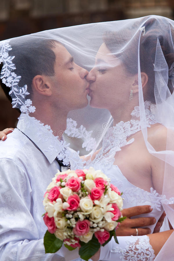 Braut- und Bräutigamküssen lizenzfreie stockbilder