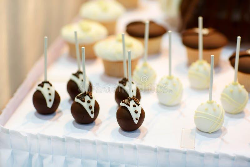 Braut- und Bräutigamkuchen knallt für die Heirat der süßen Tabelle lizenzfreie stockfotografie