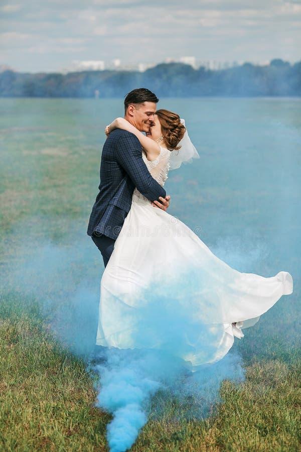 Braut- und Bräutigamtanzen im blauen Rauche auf Wiese lizenzfreies stockfoto