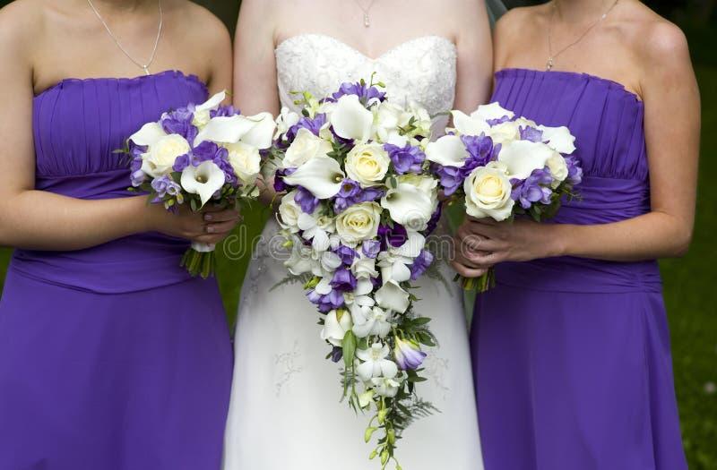 Braut und Brautjunfern mit Hochzeitsblumensträußen lizenzfreies stockbild