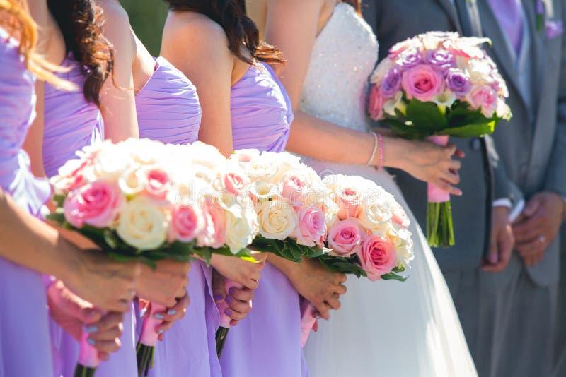 Braut und Brautjungfern, die Blumensträuße halten stockbilder