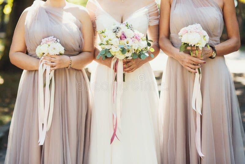 Braut und Brautjungfern mit Herbstblumensträußen lizenzfreie stockfotos