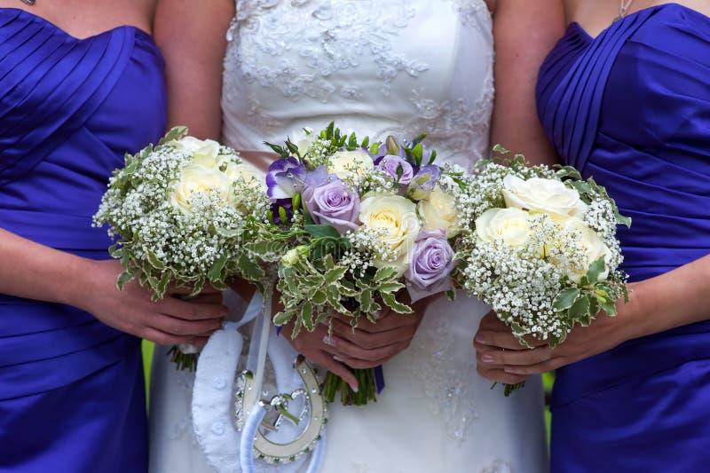 Braut und Brautjungfern mit Hochzeitsblumensträußen stockfotos