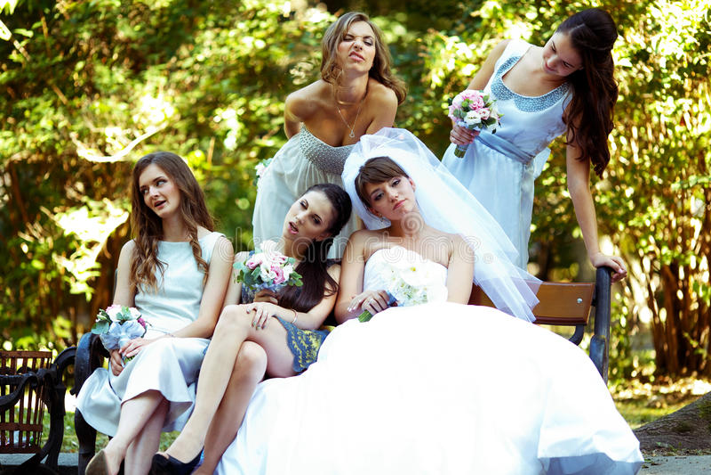 Braut- und Brautjungferngrimasse, die auf der Bank im Park sitzt stockfotos
