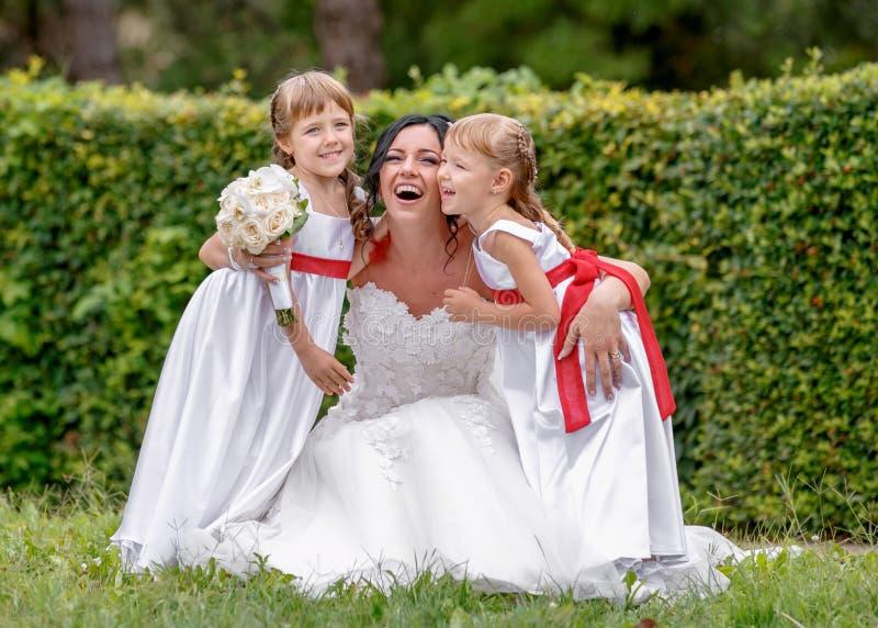 Braut und kleine Zwillingsbrautjungfer, Brautpartei stockbilder