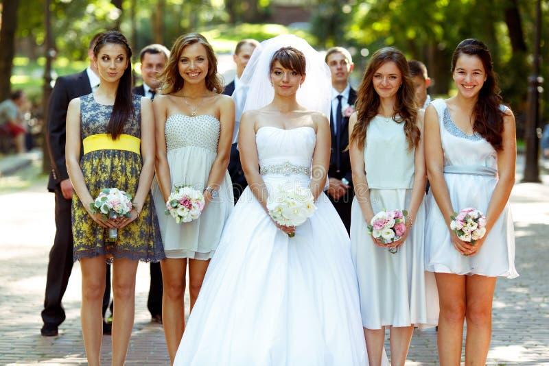 Braut und Mädchen stehen im Strahl, der im Park aufwirft stockfotografie