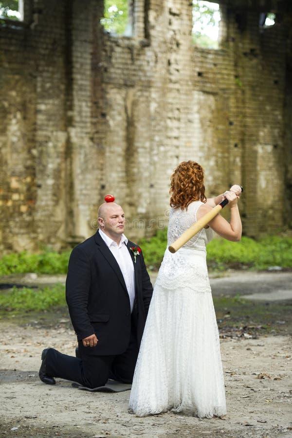 Braut versucht, einen Apfel von einem Bräutigamkopf mit einem Baseballschläger zu schlagen stockfoto