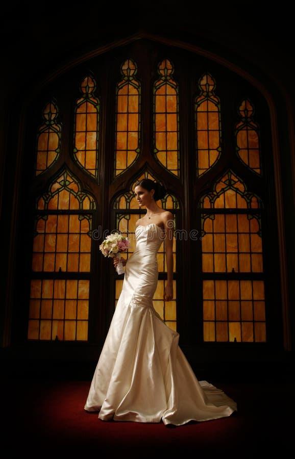 Braut vor Buntglasfenster lizenzfreie stockbilder