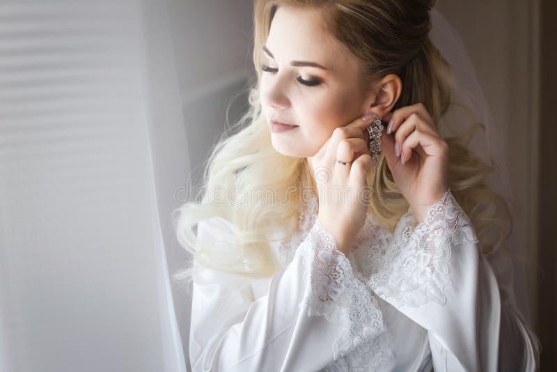 Braut in weißes peignoir tragenden Ohrringen stockfoto