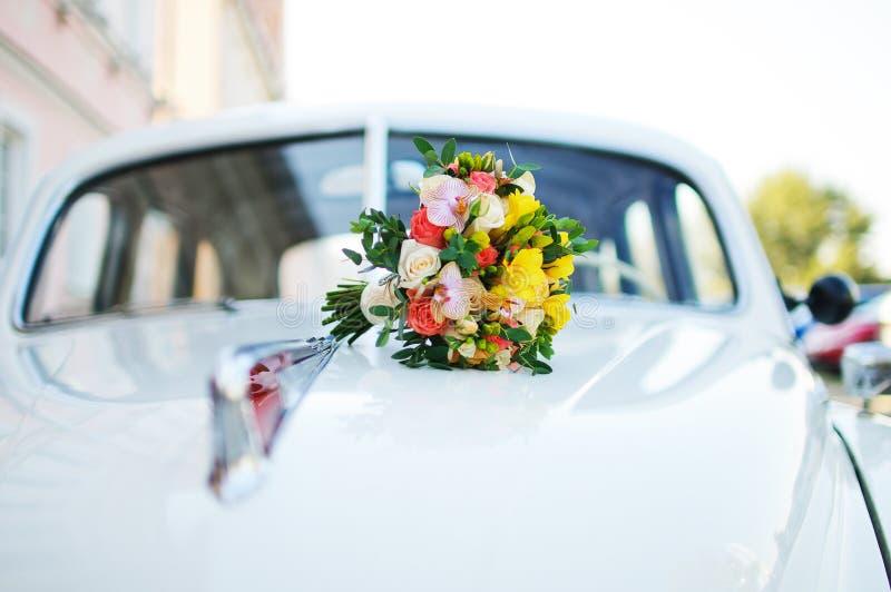 Brautblumenstrauß auf der Haube des Fahrzeugs Retro- stockbilder