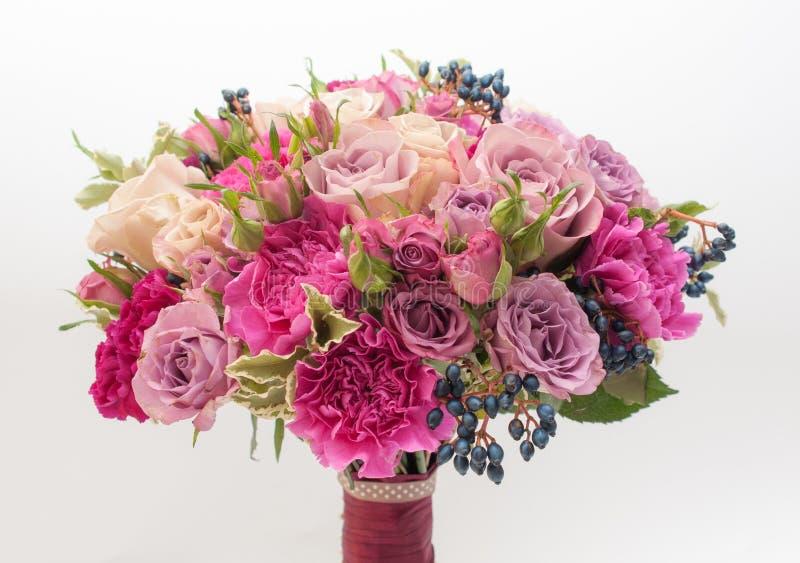Brautblumenstrauß der süßen purpurroten Rosen und der blauen Beeren lizenzfreie stockfotografie