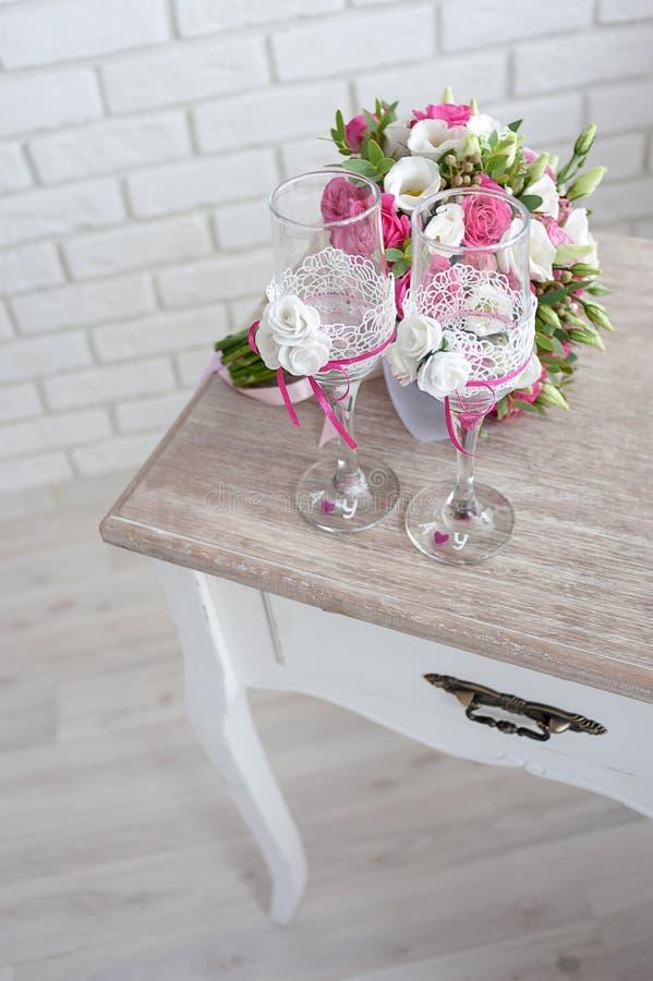 Brautblumenstrauß mit Eheringen und Weingläsern auf dem Tisch morgens des Tages stockfotografie