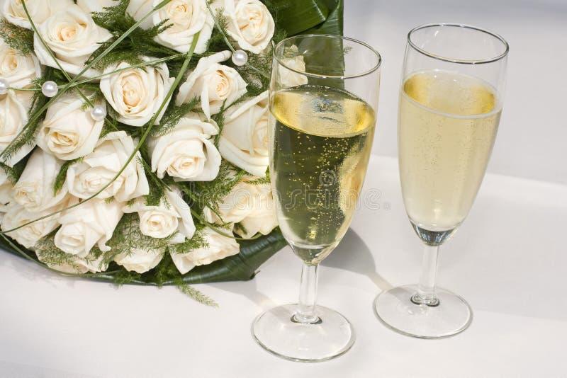Brautblumenstrauß und Champagner lizenzfreie stockbilder