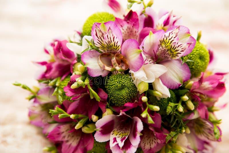 Brautblumenstrauß- und -Hochzeitsgoldringe stockfotos