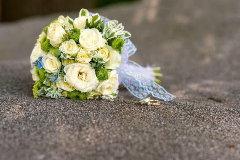 Brautblumenstrauß von gelben Rosen und von Eheringen über grauem Stein lizenzfreies stockbild