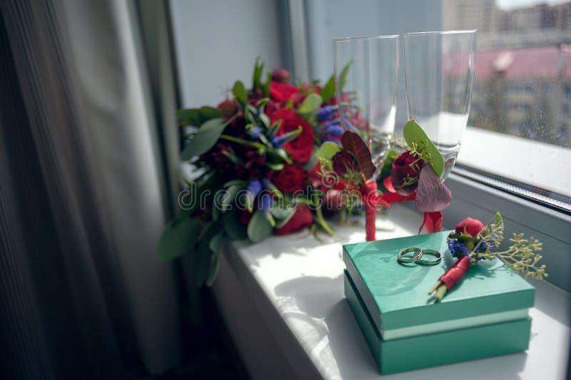 Brautblumenstrauß von roten Rosen vor der Hochzeit mit Ringen und Weingläsern steht auf dem Fenster, welches die Straße übersieht stockbilder