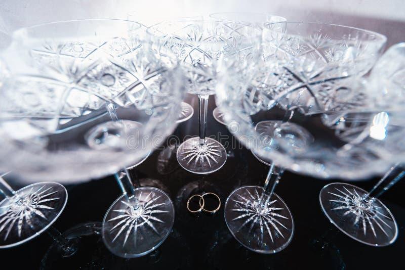 Brautdetails - Eheringe während Braut, die vor der Zeremonie fertig wird - Weinlesekristallweingläser stockfotos